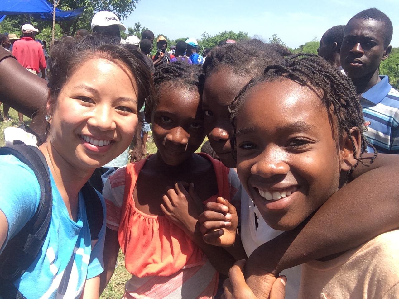 Linnette poses with children in Haiti.